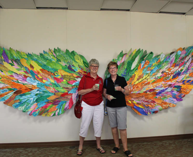 Two residents pose in front of art at Ebenezer Ridges Campus in Burnsville, Minnesota.