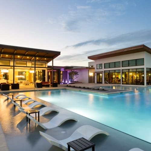 Beautifully illuminated resort-style swimming pool area at twilight at The Davis in Fort Worth, Texas