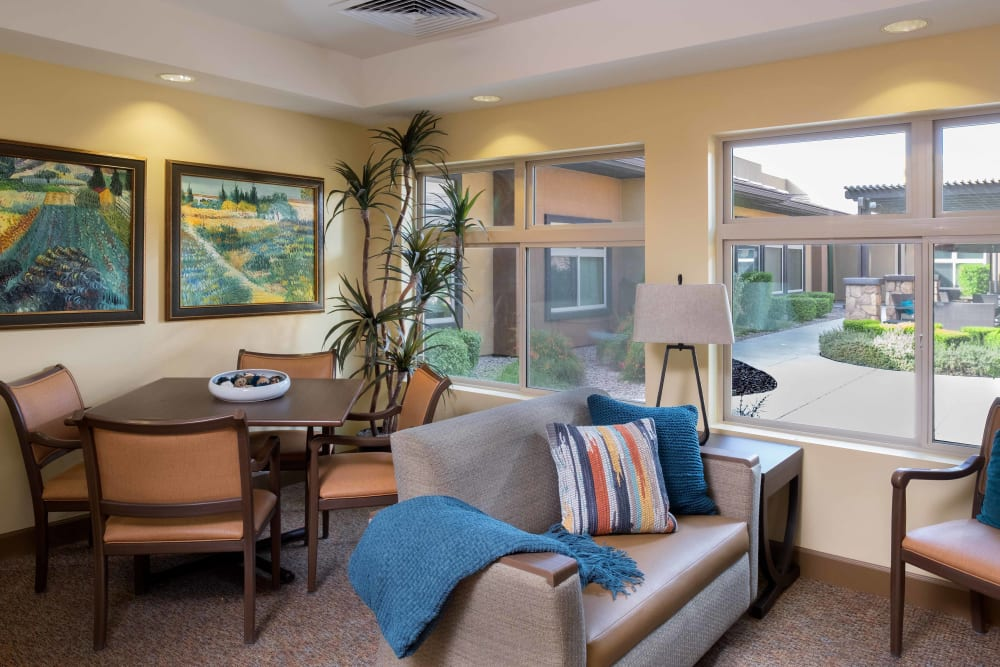 Cozy seating with a view of the courtyard at Avenir Memory Care at Chandler in Chandler, Arizona