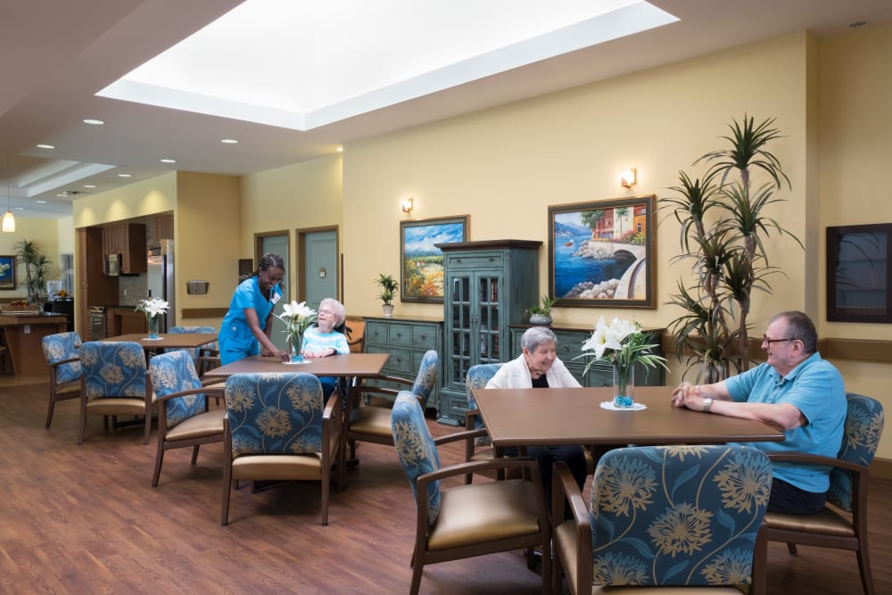 Residents and a caretaker in the dining room at Avenir Memory Care at Chandler in Chandler, Arizona
