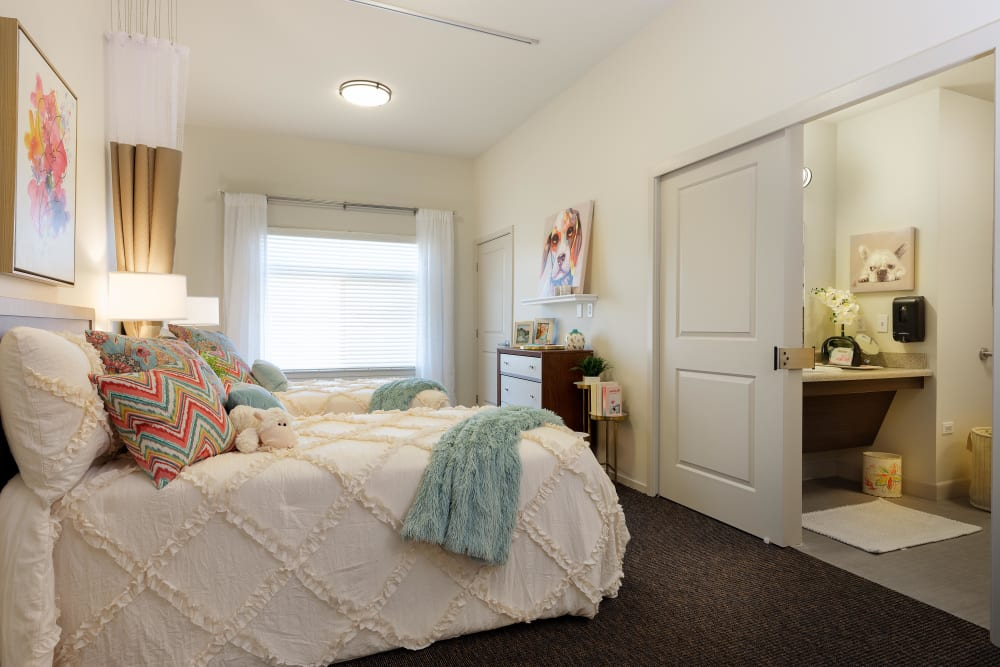 Model resident shared bedroom with window at Avenir Memory Care at Summerlin in Las Vegas, Nevada.