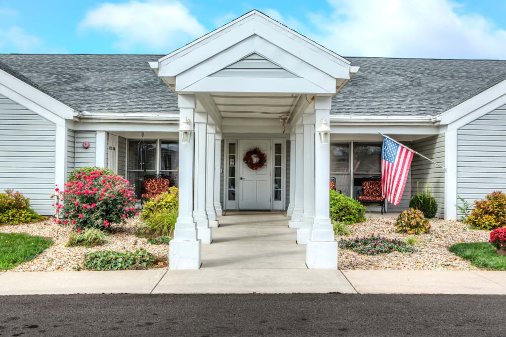 Sunny entranceway to upscale senor living facility with american flag at Carriage Court of Grove City in Grove City, Ohio