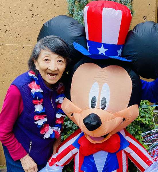 A First Hill (WA) poses next to a festive Mickey Mouse for Independence Day.