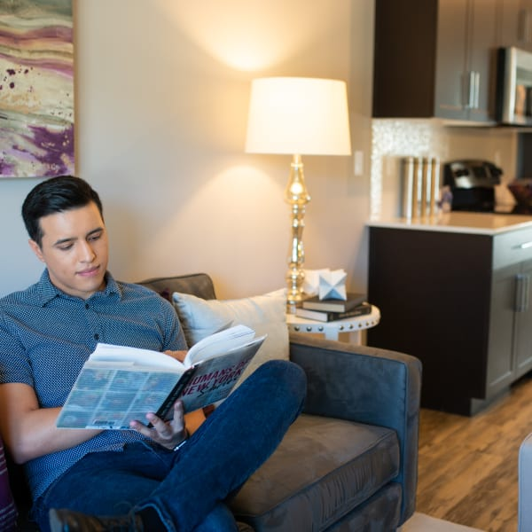Resident relaxing with a book in his new home at The Retreat at the Raven in Phoenix, Arizona