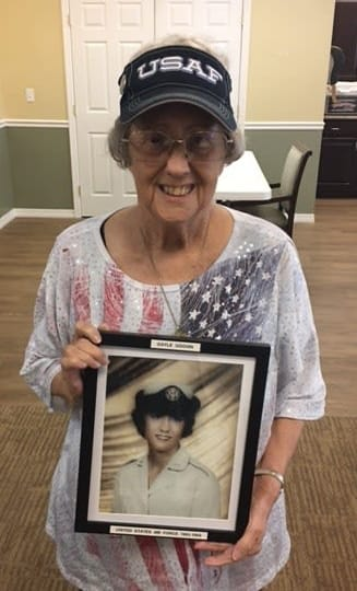 Gayle, Barkley Place resident, poses with her military photo from the 1960s.
