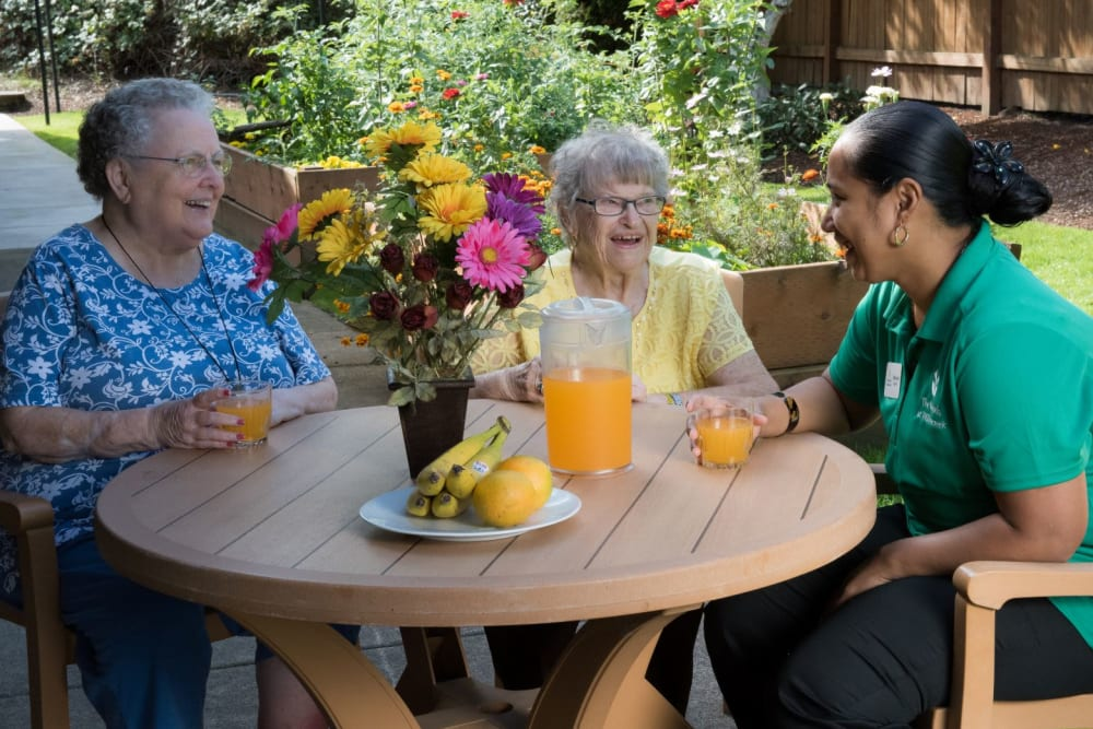 Two residents sitting outside enjoying a beverage with a staff member on a sunny day complete with sunflower centerpiece at The Springs at Willowcreek in Salem, Oregon