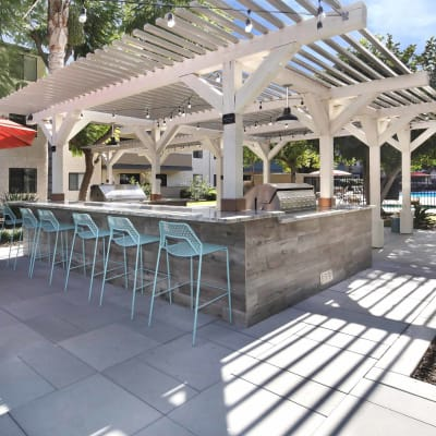 Barbecue area with gas grills and pergola at Haven Warner Center in Canoga Park, California