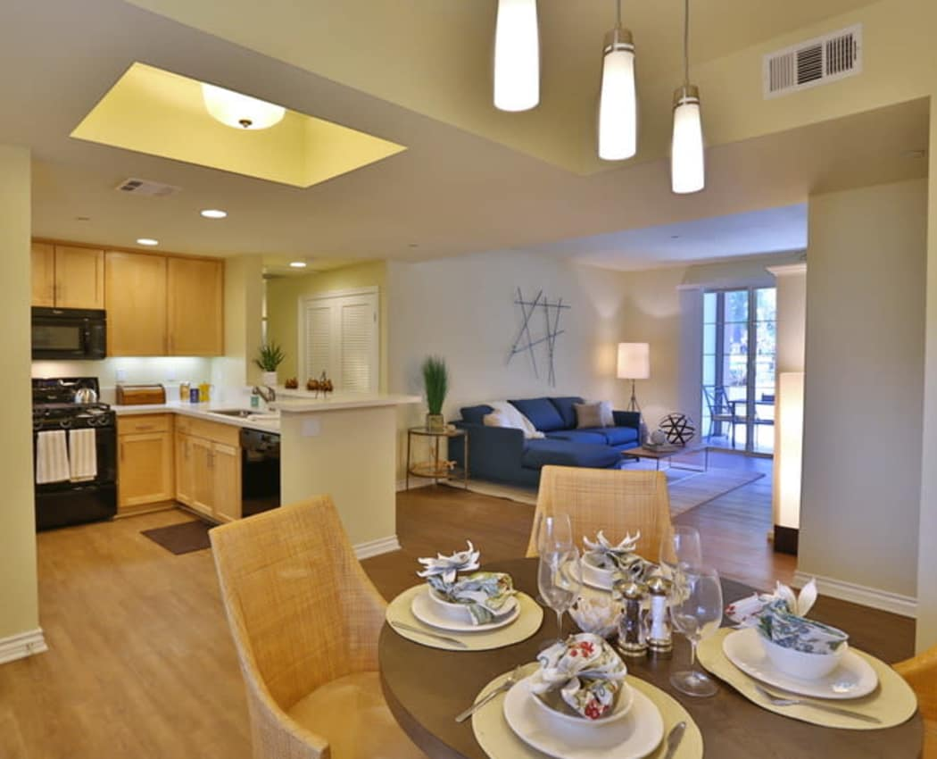 View of the kitchen and living space from a model home's dining area at IMT Park Encino in Encino, California