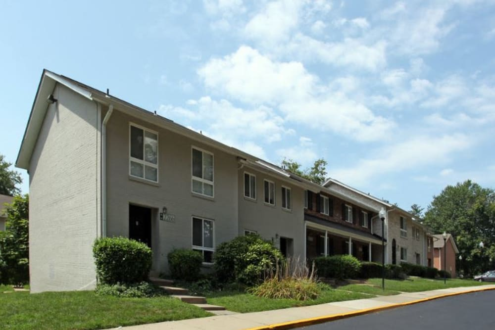 Beautiful exterior of apartment building with a well manicured landscape at Glenmont Crossing in Wheaton, Maryland