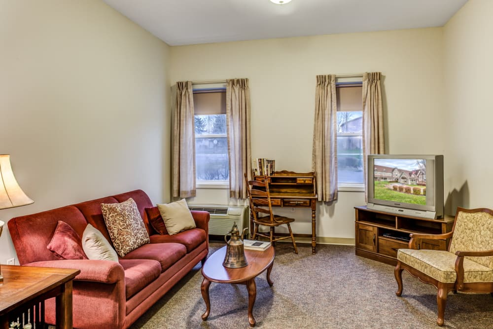 Living room of apartment unit with comforable seating and television set at Grand Victorian of Sycamore in Sycamore, Illinois