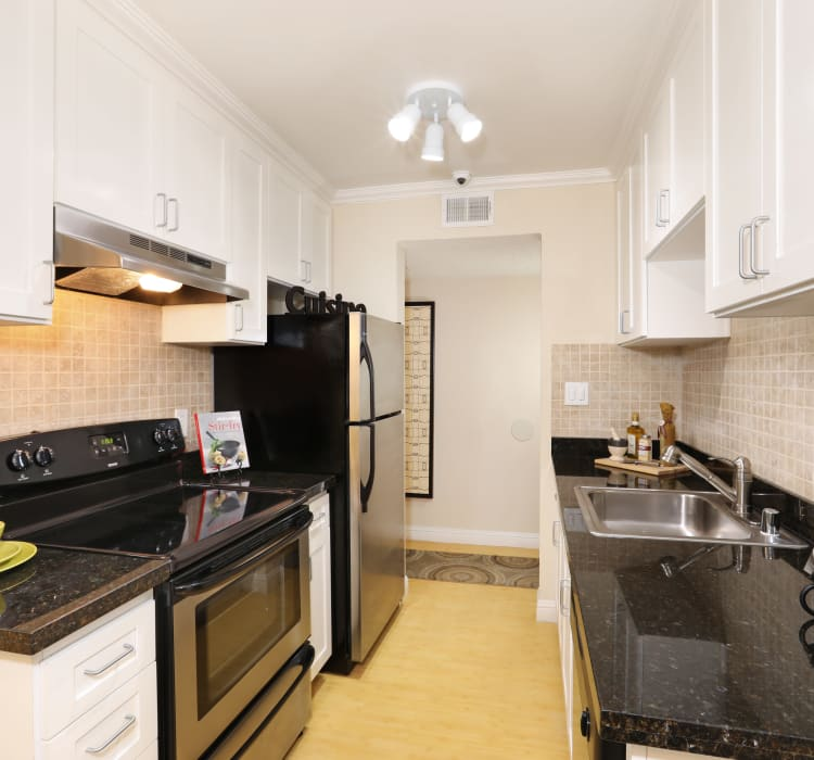 Recently renovated kitchen with sleek black appliances in a model home at Sofi Redwood Park in Redwood City, California