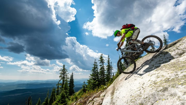 Man on a mountain bike riding downhill on granite with trees and views of mountains in the background.