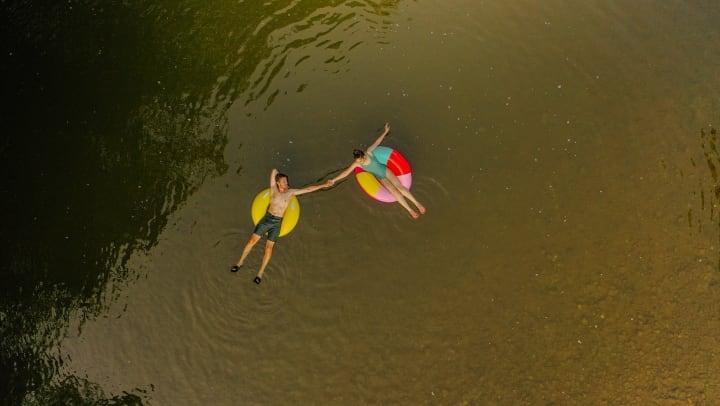 Overhead shot of couple on innertubes floating down river