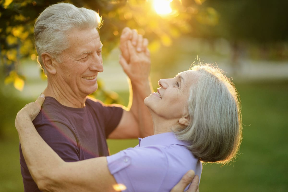 Resident couple dancing outside at Oxford Villa Active Senior Apartments in Wichita, Kansas