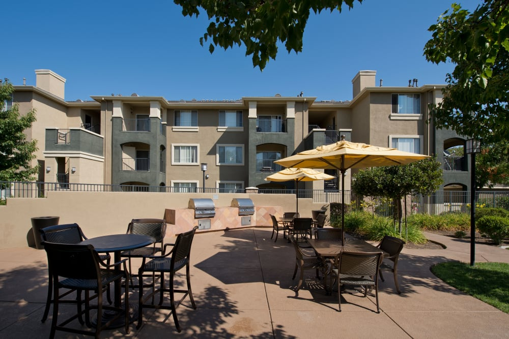 Community patio with barbecue grills and seating for entertaining guests at Cross Pointe Apartment Homes in Antioch, California