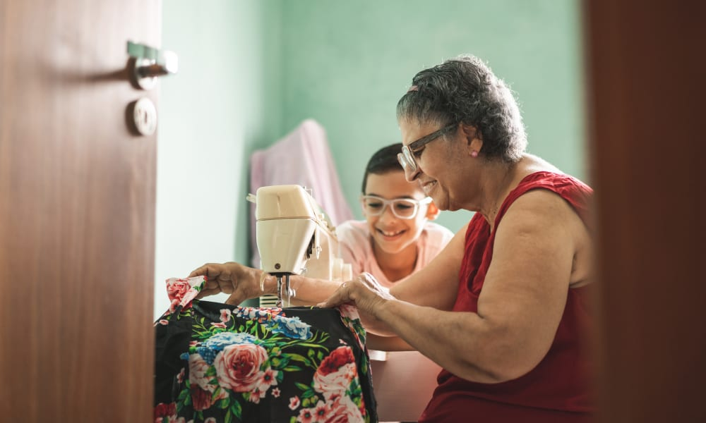 A resident and child sewing at Ativo Senior Living of Prescott Valley in Prescott Valley, Arizona.