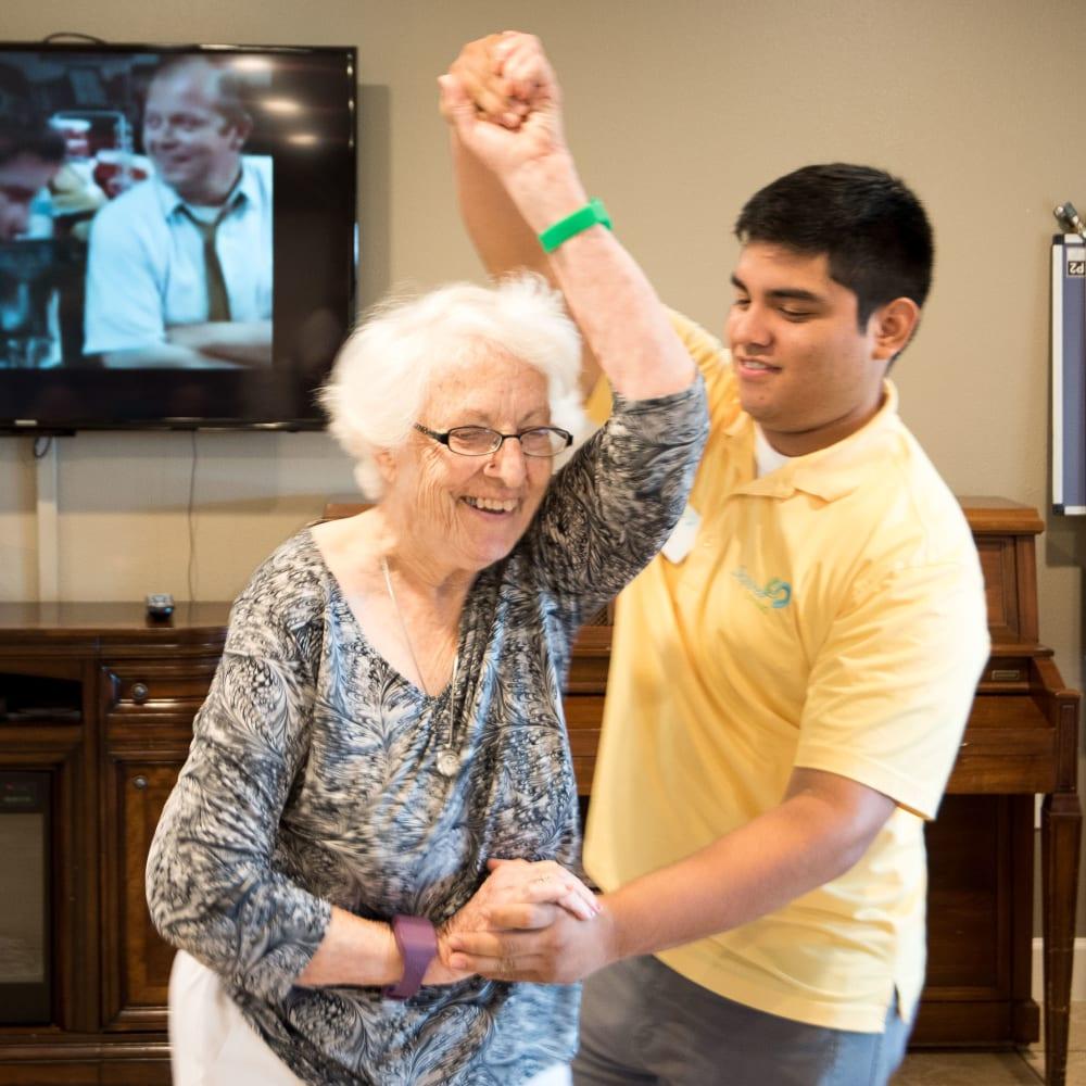 Resident and staff member dance at Inspired Living Bonita Springs in Bonita Springs, Florida