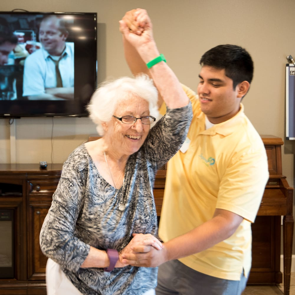 Resident and staff member dance at Inspired Living Sugar Land in Sugar Land, Texas