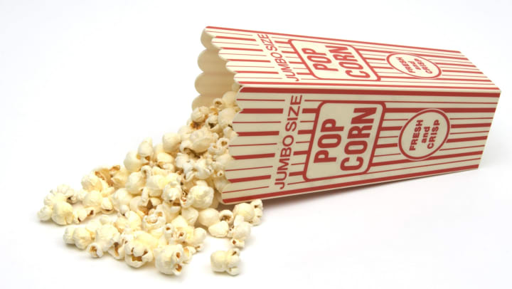Popcorn spilling from red and white popcorn box