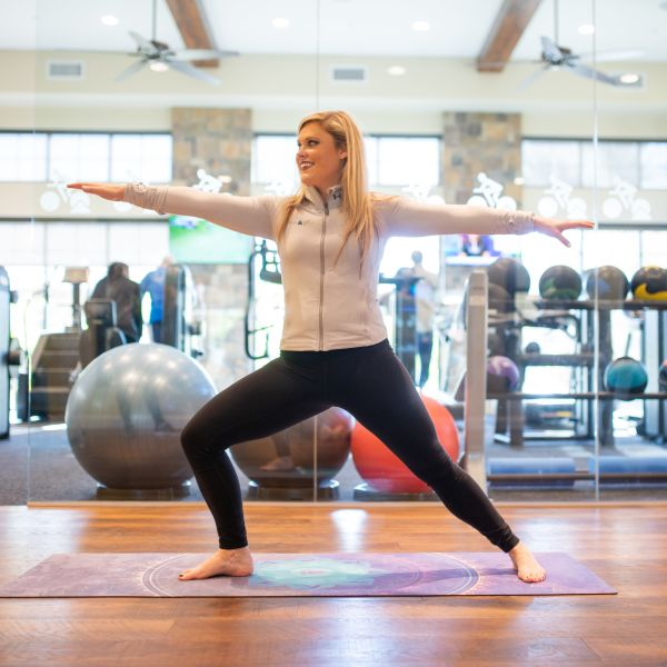 Resident practicing yoga in the gym at Club Cancun in Chandler, Arizona