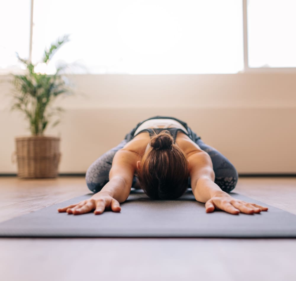 Resident stretching on a yoga mat in the onsite fitness center at Haven Apartment Homes in Kent, Washington