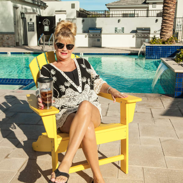 Resident relaxing with a drink poolside at Christopher Todd Communities At Marley Park in Surprise, Arizona