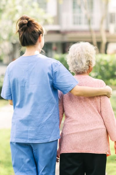 Memory care resident walking outside with a caretaker at Quail Park of Granbury in Granbury, Texas