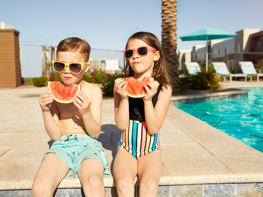 Two young residents eating watermelon by the pool at BB Living at Val Vista in Gilbert, Arizona