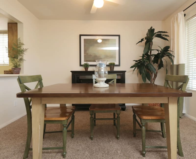 Well-furnished dining area with plush carpeting and a ceiling fan in a model home at Overlook Point Apartments in Salt Lake City, Utah
