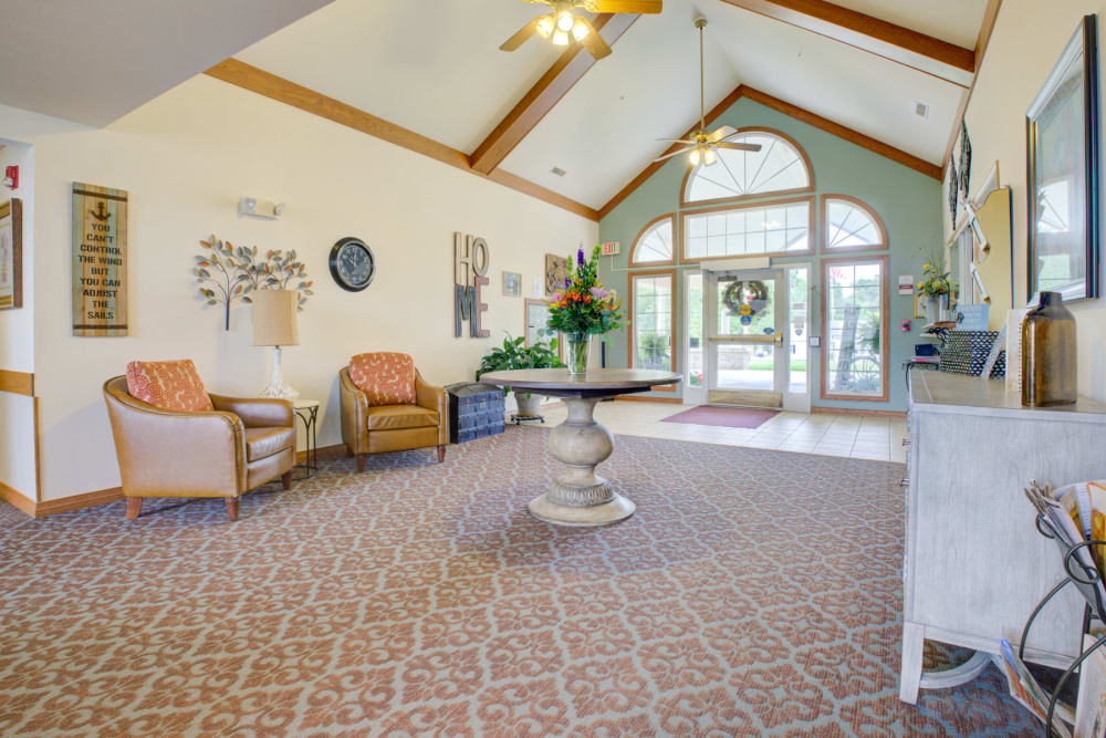 Airy open space with welcoming flowers and armchair seating at Brookstone Estates of Vandalia in Vandalia, Illinois