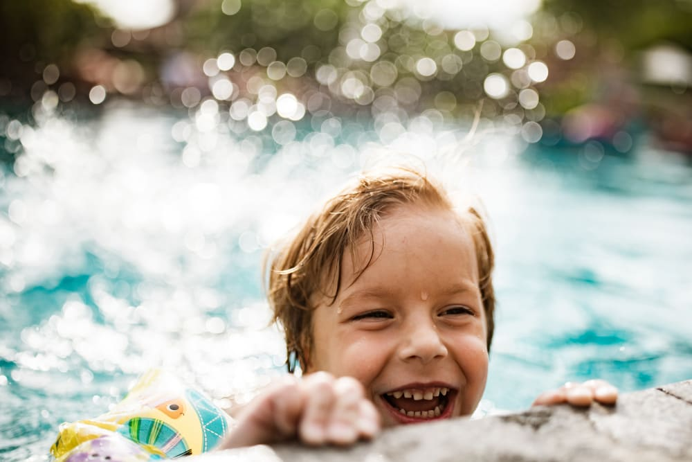 Child having a ball in the pool at Paloma Summit Condominium Rentals in Foothill Ranch, California