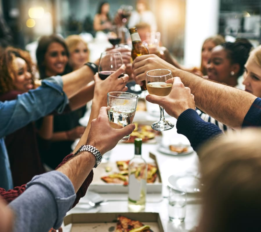 Group of resident friends out for a meal at their favorite restaurant and raising a toast to the good life at Verse Seattle in Seattle, Washington