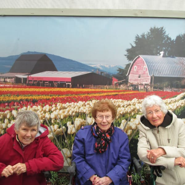 3 women standing in front of a mural of tulips at Quail Park Memory Care Residences of Visalia in Visalia, California