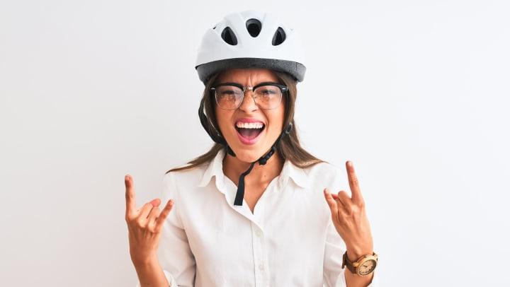 Woman wearing helmet making Devil horns with her hands.