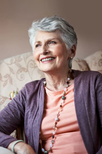 Resident sitting on a couch and smiling at Quail Park Memory Care Residences of Visalia in Visalia, California