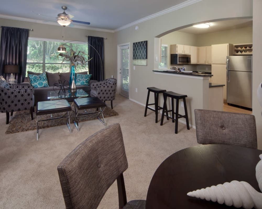 Beautifully furnished open-concept living area with plush carpeting in a model home at Wimberly at Deerwood in Jacksonville, Florida