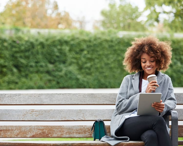 Resident reading her iPad in the park near Domus on the Boulevard in Mountain View, California