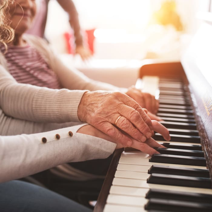 A resident playing piano with her granddaughter at Milestone Senior Living in Hillsboro, Wisconsin