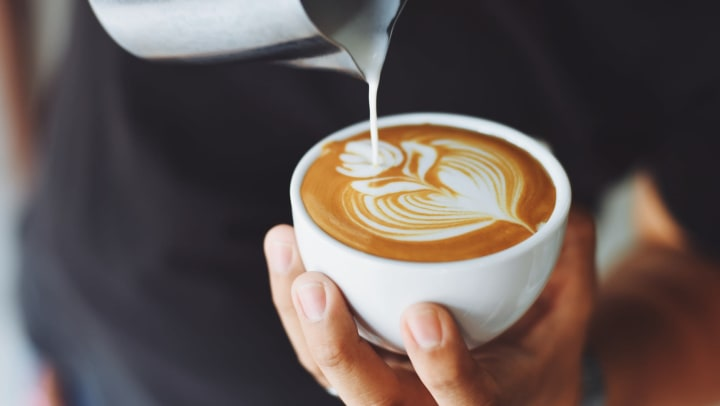 Barista pouring a cup of coffee near Lux on Main in Carrollton, Texas