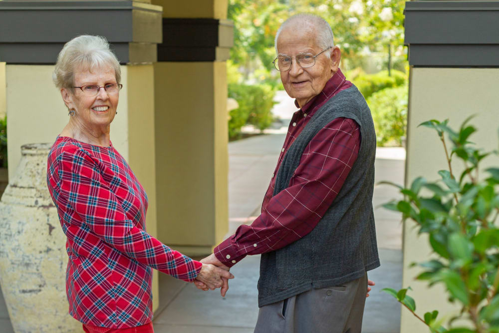 Resident couple holding hands at Merrill Gardens at Campbell