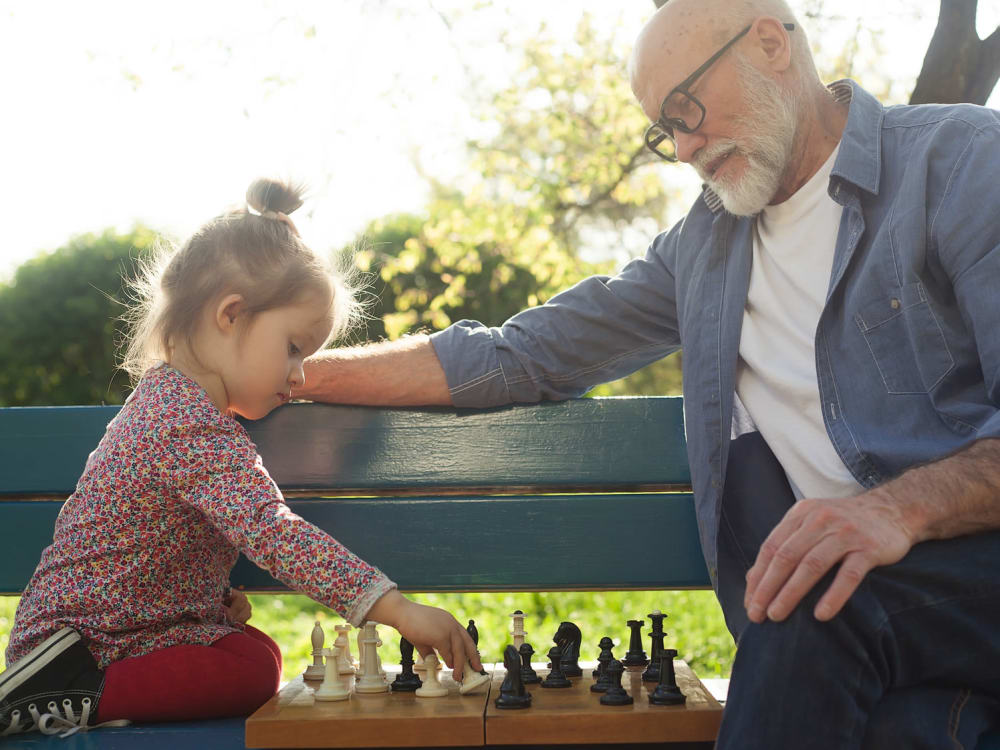 A resident playing chess with a young child at Touchmark Central Office in Beaverton, Oregon