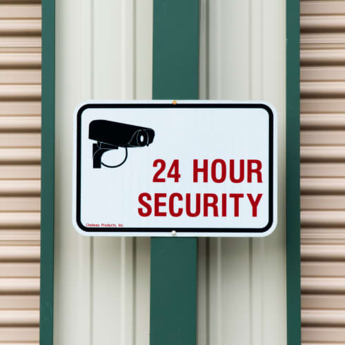 A sign for 24 hour security at Red Dot Storage in Bloomington, Illinois