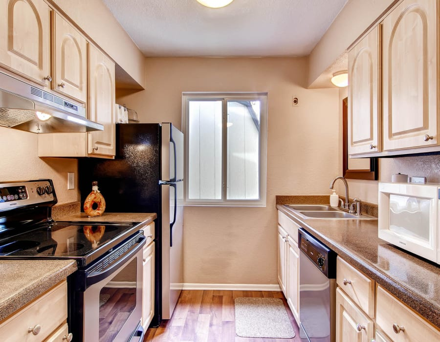 Spacious kitchen with wood-style plank flooring at Arvada Green Apartment Homes in Arvada, Colorado