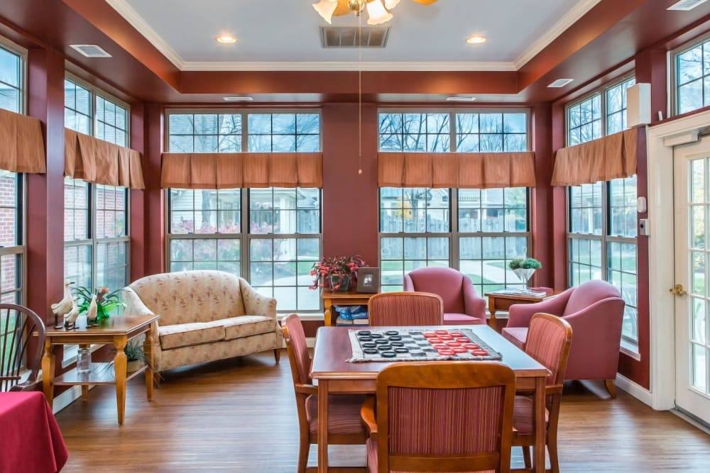 Charming game room with tract lighting, wood accents, armchairs and chess set at Carriage Court of Lancaster in Lancaster, Ohio
