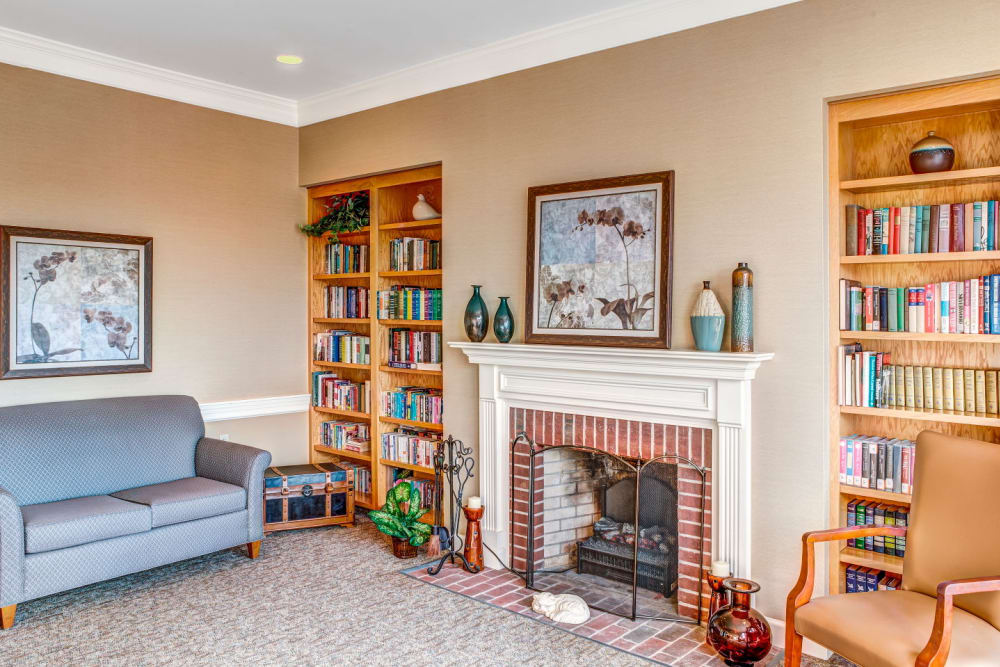 Reading room with copious books in elegant wood bookcase and fireplace at Carriage Court of Lancaster in Lancaster, Ohio