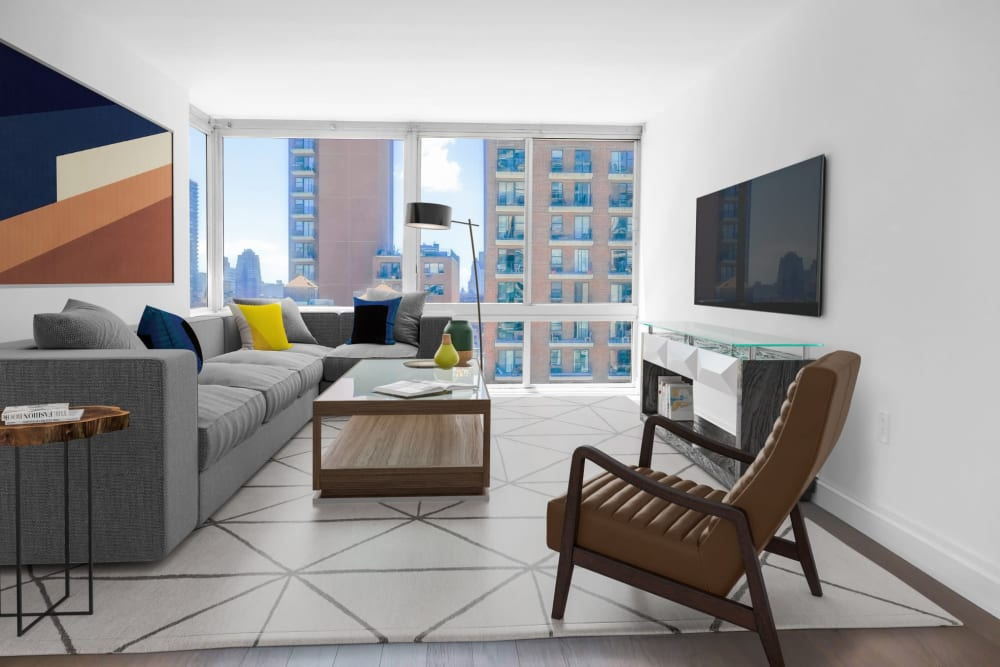 Spacious living room area with a large window at The Ventura in New York, New York