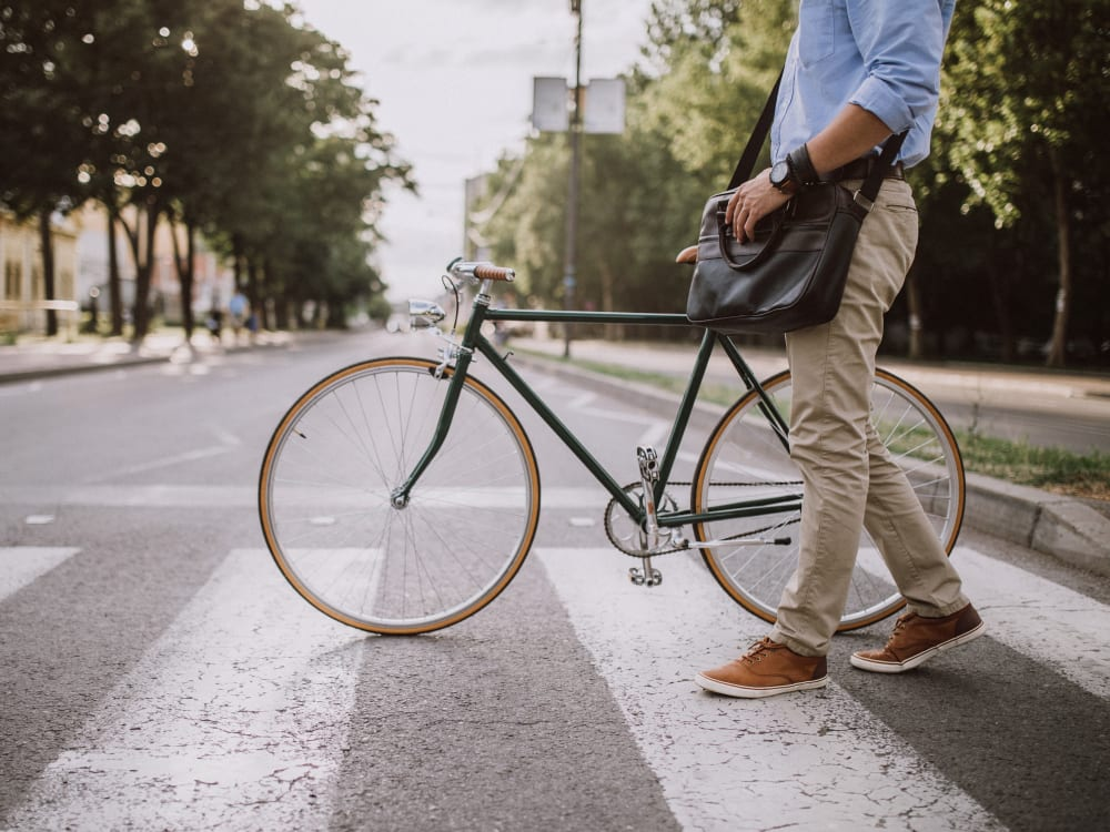 Man walking his bike across a crosswalk on his way to work at Terra Apartment Homes in Federal Way, Washington