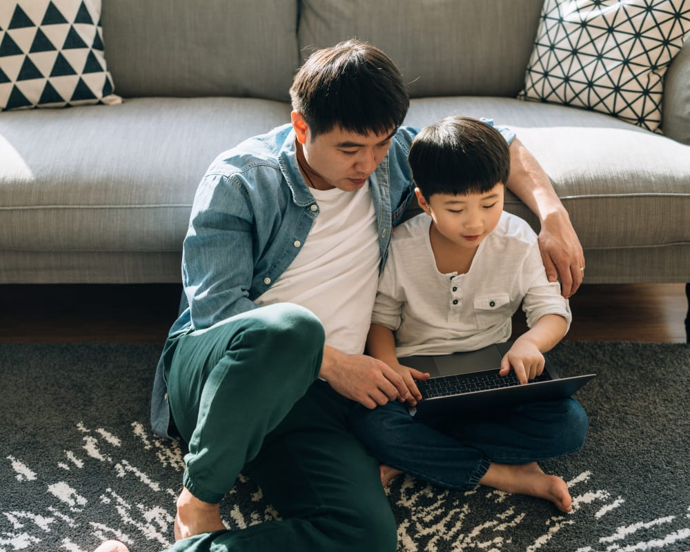 Father teaching his son to use a laptop in their new home at Sofi Irvine in Irvine, California