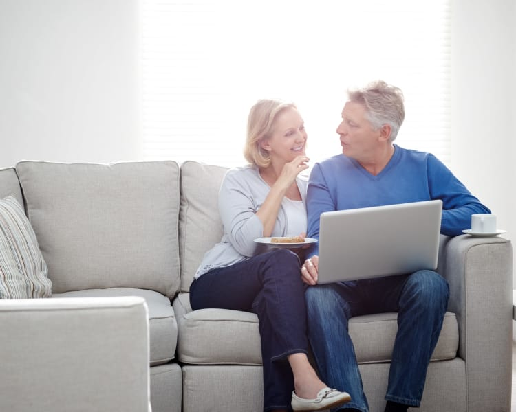 Older couple sitting on a gray couch together at Haddon Knolls Apartments